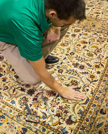 area rug cleaner examining an oriental rug